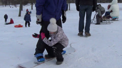 Follow view of father slide on snowboard with girl on hill Stock Footage
