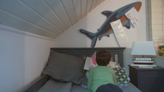 Little boy reading an illustrated book in bed, child in his room at home Stock Footage