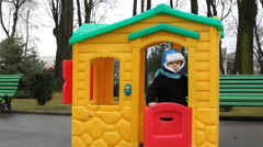 Cute kid playing in a colored little house in the park, say goodbye, farewell,  Stock Footage