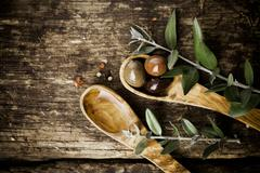 olive wood spoons with fresh olives - stock photo