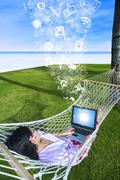 Asian woman using laptop on hammock at beach Stock Illustration