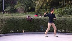 A man practices martial arts in Kowloon Park Hong Kong Stock Footage