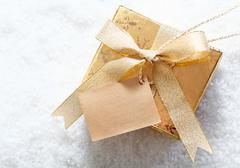 gold gift box with blank tag in snow - stock photo