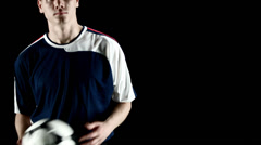 A soccer player tosses the ball back and forth in his hands Stock Footage
