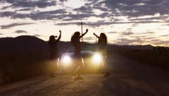 Three Teen Girls Dancing In Car Headlights On A Remote Dirt Road At Dusk Stock Footage