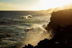 Waves crashing on ocean cliffs at sunset - stock photo