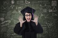 Stock Photo of excited female graduate and written board