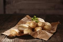 pile of fresh potatoes on brown paper - stock photo
