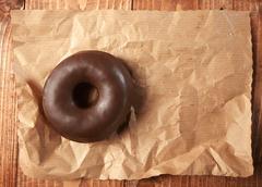 Tasty chocolate doughnut on a paper Stock Photos
