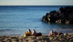 Women sunbathing on Hawaiian beach - stock photo
