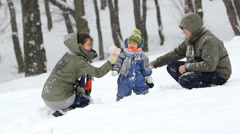 Snowball fight, happy young family with little kid in snow Stock Footage