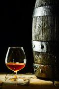 cognac snifter and an old oak barrel - stock photo