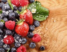 assortment of berries over a wood table - stock photo