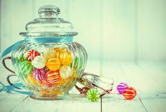 antique candy jar filled with candies metal tongs - stock photo