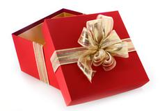 Open gift box with tilted lid and gold bow Stock Photos