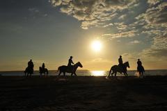 Horse riders on beach Stock Photos