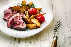 Roast beef steak with potato wedges and tomato Stock Photos