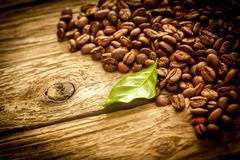 Background of coffee beans on rustic driftwood Stock Photos