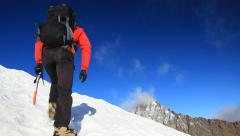 Mountaineer climbing a snowy mountain in winter season Stock Footage