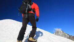 Lone mountaineer climbing a snowy ridge in winter season. - stock footage