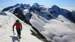 Mountaineer walks along the snowy ridge of Breithorn Stock Footage