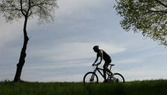 Male mountain bike cyclist riding uphill along a country road; clear summer day Stock Footage