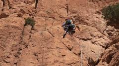 Climber climb a rock wall. Todra Gorge, Atlas, Maroc, Africa. Stock Footage