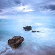 rocks in a ocean waves under cloudy sky. bad weather. - stock photo