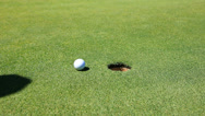 Stock Video Footage of Golfer sinks a putt, then retrieves golf ball - HD1080P