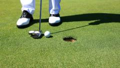 Golfer sinks a putt, then retrieves golf ball - HD1080P - stock footage