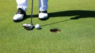 Golfer sinks a putt, then retrieves golf ball - HD1080P Stock Footage