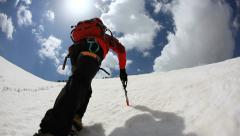 Mountaineer walking uphill along a snowy slope. Rear view. Western Alps, Europe. Stock Footage