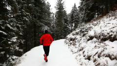 Winter trail running: man takes a run on a snowy mountain path in a pine woods - stock footage
