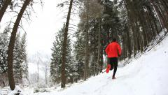 Winter trail running: man takes a run on a snowy mountain path in a pine woods. Stock Footage