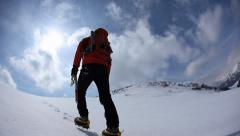 Mountaineer walking uphill along a snowy slope. Rear view. Western Alps, Europe. - stock footage