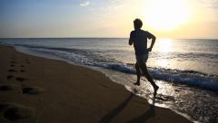 Man running on beach at sunrise. HD1080P by Canon 5DMkII - stock footage