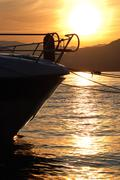small boat anchored in quite lake water before the dawn - stock photo
