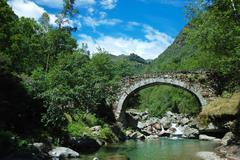 aged arch bridge over a small mountain river - stock photo