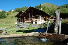 """Stock Photo of fountain of a tipical rural mountain wooden house """"walser"""", italy-swiss border."""