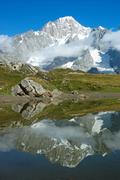 Stock Photo of view of the south face of mont blanc mountain range reflected in a small lake, v