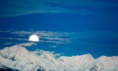 Stock Photo of moonset behind snowed mountain
