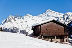Stock Photo of wooden cottage over snowed mountain