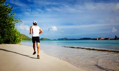 man running on a tropical beach - stock photo