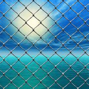 freedom - link fence over sunny sky and sea - stock illustration