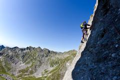 Stock Photo of caucasian male climber climbing a steep wall