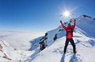 Stock Photo of mountaineer reaches the top of a snowy mountain in a sunny winter day.