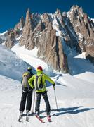 skiers in front of the breathtaking view of mont blanc de tacul - stock photo