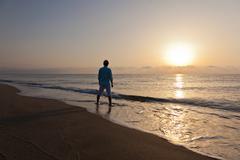 Stock Photo of man alone on beach watching the sunset