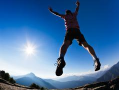man jumping in the sunshine against blue sky - stock photo