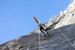 a rock climber abseiling off a climb - stock photo